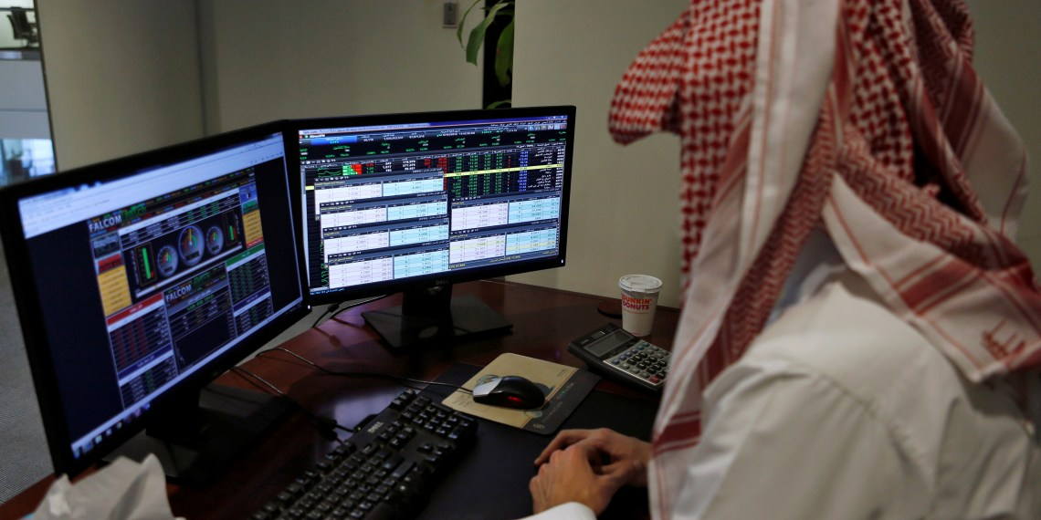 FILE PHOTO: A Saudi trader observes the stock market on monitors at Falcom stock exchange agency in Riyadh, Saudi Arabia February 7, 2018. REUTERS/Faisal Al Nasser
