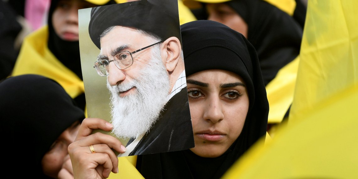 FILE PHOTO: A woman carries a picture of Iran's Supreme Leader Ayatollah Ali Khamenei as she watches Lebanon's Hezbollah leader Sayyed Hassan Nasrallah appear on a screen during a live broadcast to speak to his supporters at an event marking Resistance and Liberation Day in the Bekaa Valley, Lebanon, May 25, 2017. REUTERS/Hassan Abdallah/File Photo