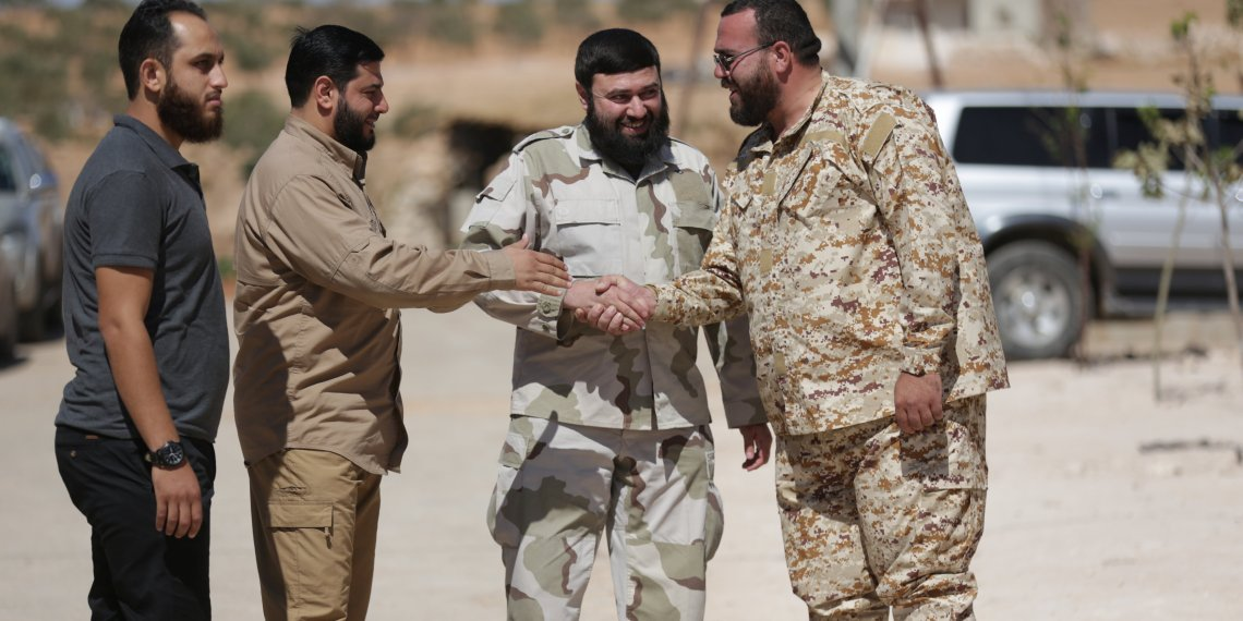 Jaish al-Islam commander Issam al-Buwaydani, shakes hands with an army commander in Jaish al-Islam in the town of Soussian in Aleppo countryside, Syria September 23, 2018. Picture taken September 23, 2018. REUTERS/Khalil Ashawi