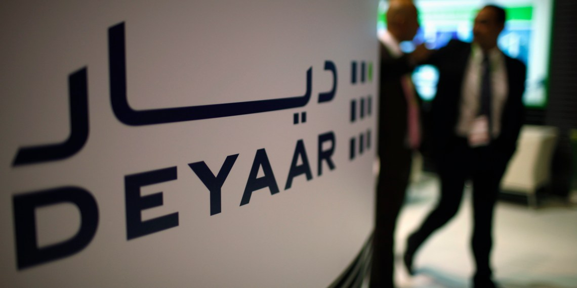 FILE PHOTO: Visitors walk past the stand belonging to real estate developer Deyaar during the Cityscape real estate exhibition in Dubai October 2, 2012. REUTERS/Ahmed Jadallah