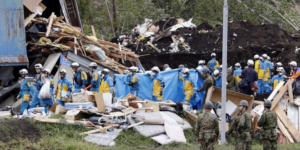 Police officers and members of the Japan Self-Defense Forces (JSDF) carry a missing person found from an area damaged by a landslide caused by an earthquake in Atsuma town, Hokkaido, northern Japan, in this photo taken by Kyodo September 8, 2018. Mandatory credit Kyodo/via REUTERS