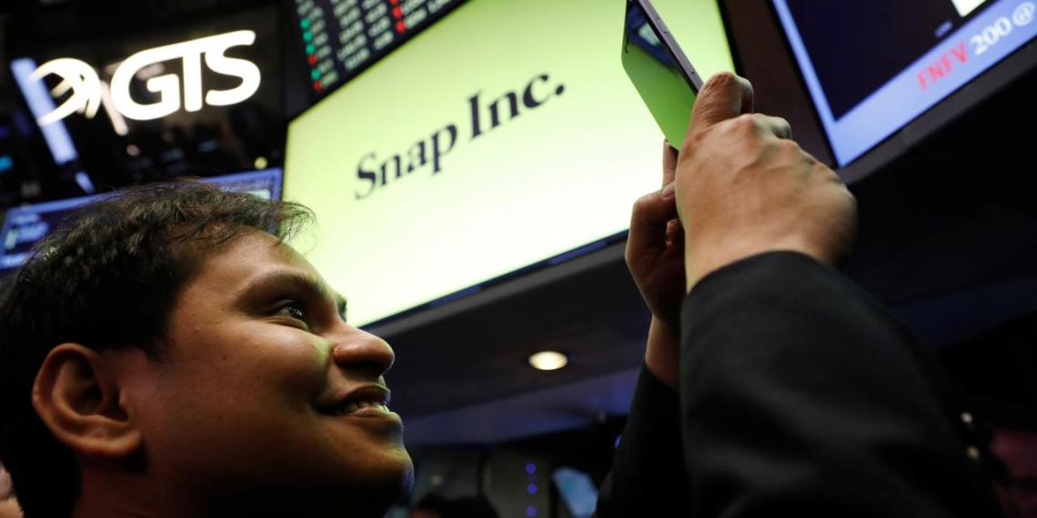 FILE PHOTO - Snap Inc. chief strategy officer, Imran Khan, takes a photograph on the floor of the New York Stock Exchange (NYSE) while waiting for Snap Inc. to post their IPO in New York, U.S., March 2, 2017. REUTERS/Brendan McDermid