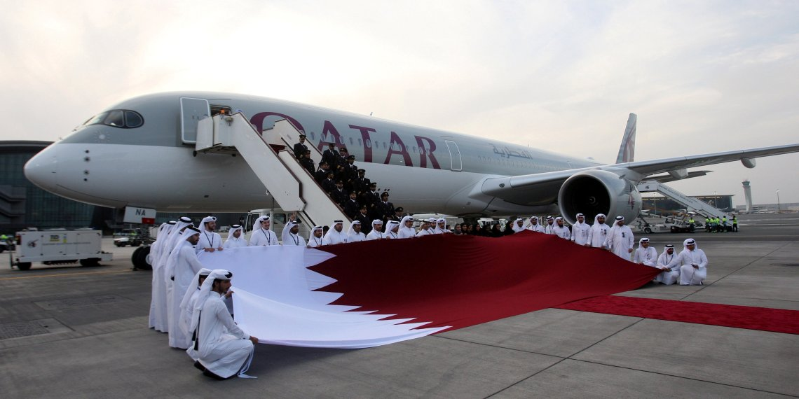 FILE PHOTO: Qatar Airways staff hold a Qatari flag in front of an Airbus A350-1000 at Hamad International Airport in Doha, Qatar, February 21, 2018. REUTERS/Naseem Zeitoon/File Photo