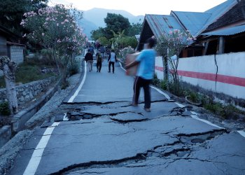 Residents walk on cracked tarmac as they carry their belongings after an earthquake hit at Balaroa sub-district in Palu, Sulawesi Island, Indonesia October 1, 2018. REUTERS/Beawiharta