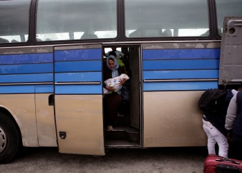 A migrant holding a baby steps off a bus before she boards the Nissos Rodos passenger ship at the port of Mytilene on the island of Lesbos, Greece September 28. REUTERS/Elias Marcou