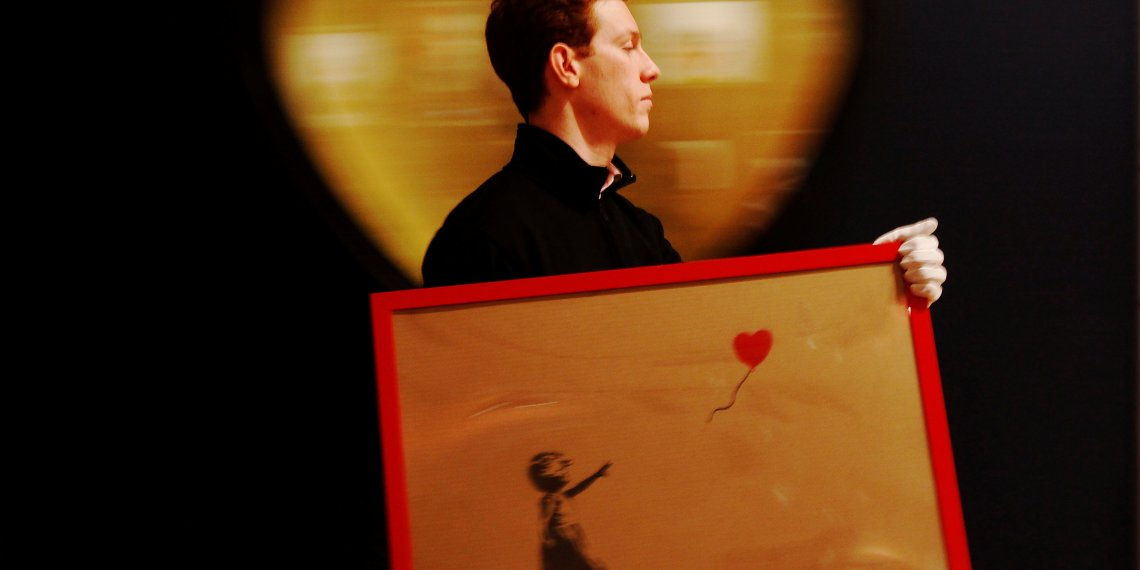"FILE PHOTO: An employee walks with Banksy's ""Girl and Balloon"" 2009, at Bonhams auction house in London March 23, 2012. REUTERS/Luke MacGregor/File Photo"