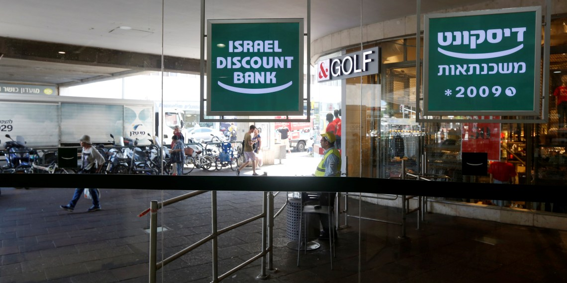 FILE PHOTO: The logo of Israel Discount Bank is reflected in mirrors outside their branch in Tel Aviv, Israel July 27, 2016. REUTERS/Baz Ratner