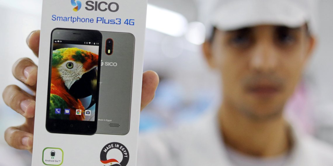 FILE PHOTO: A factory worker holds up a package of Sico mobile phone in Assuit, Egypt September 30, 2018. REUTERS/Mohamed Abd El Ghany