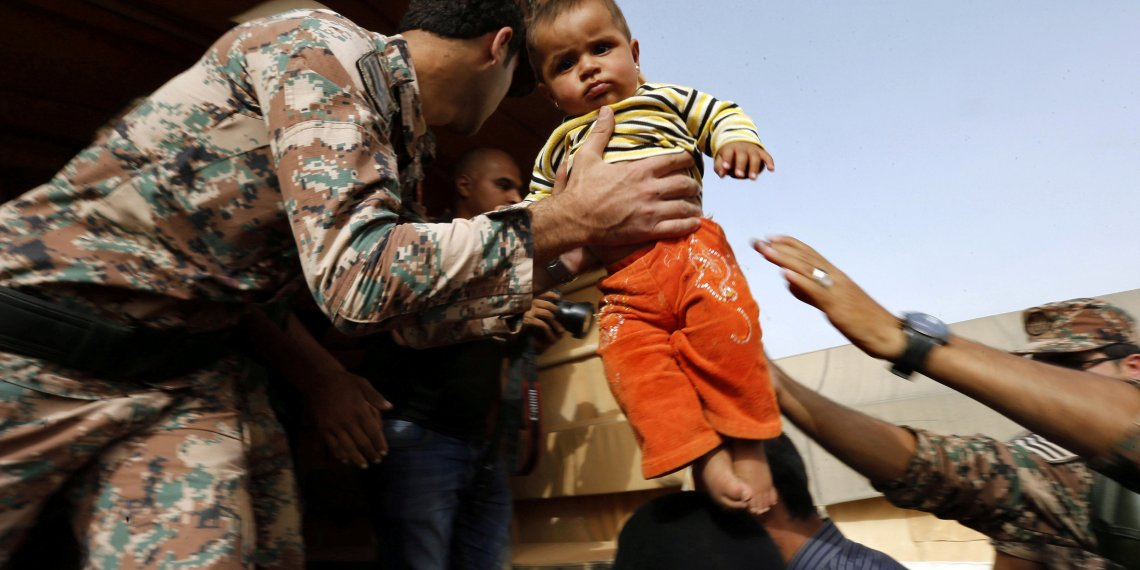FILE PHOTO: A Jordanian soldier carries a Syrian refugee child to help him board a Jordanian army vehicle with his family after they crossed into Jordanian territory, in Al Ruqban border area, near the northeastern Jordanian border with Syria, and Iraq, near the town of Ruwaished, 240 km (149 miles) east of Amman September 10, 2015. REUTERS/Muhammad Hamed
