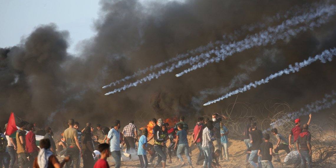 Tear gas canisters are fired by Israeli troops towards Palestinian demonstrators during a protest calling for lifting the Israeli blockade on Gaza and demanding the right to return to their homeland, at the Israel-Gaza border fence in the southern Gaza Strip October 12, 2018. REUTERS/Ibraheem Abu Mustafa