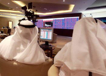 FILE PHOTO: Traders monitor screens displaying stock information at Qatar Stock Exchange in Doha, Qatar June 5, 2017. REUTERS/Stringer