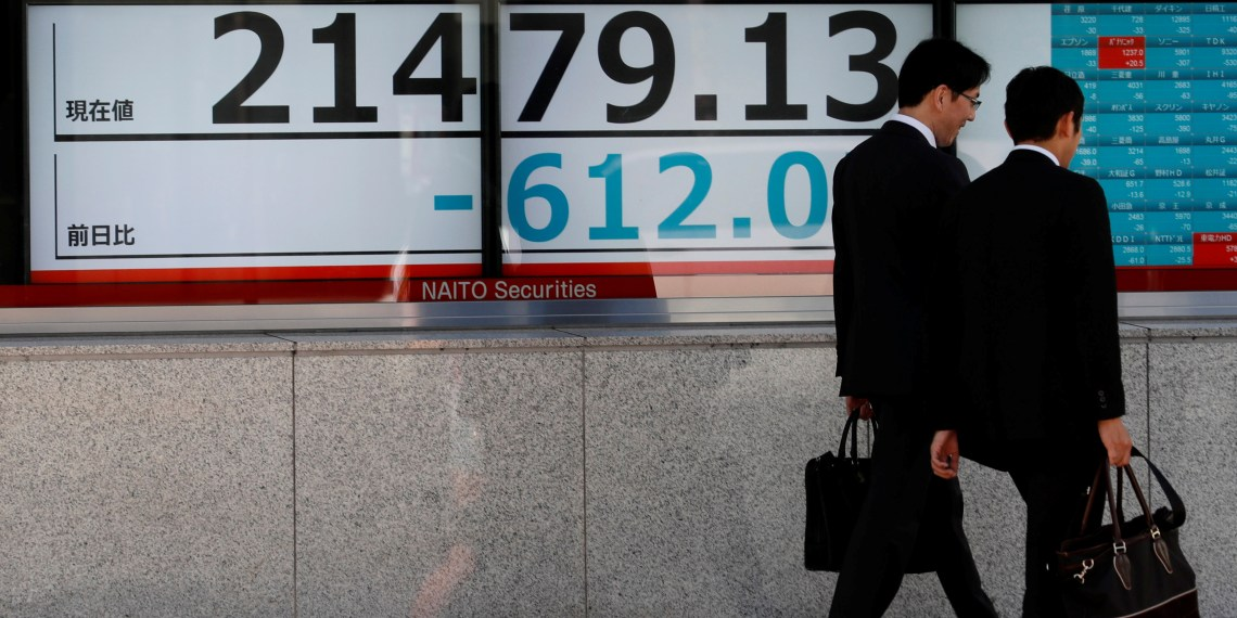 Men walk past an electronic board showing Japan's Nikkei average outside a brokerage in Tokyo, Japan, October 25, 2018. REUTERS/Kim Kyung-Hoon