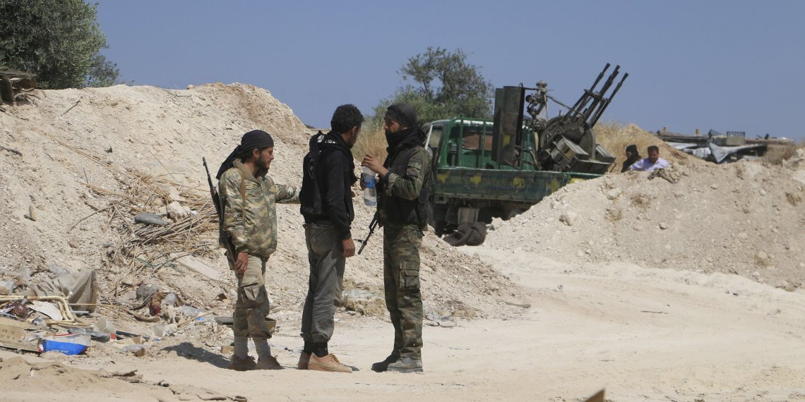 "FILE PHOTO: Fighters from a coalition of rebel groups called ""Jaish al Fateh"", also known as ""Army of Fatah"" (Conquest Army), talk near Psoncol town after saying they had taken control of it, in the Idlib countryside, Syria June 6, 2015. REUTERS/Mohamad Bayoush"