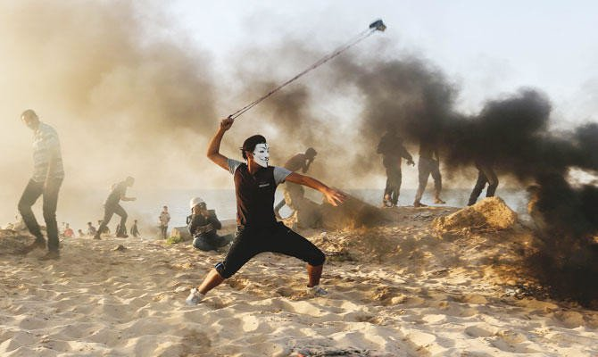 A protester uses a slingshot to hurl stones during protests in Gaza Strip. (AFP)