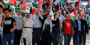 Palestinian protesters march with Palestinian flags during a demonstration. (AFP)