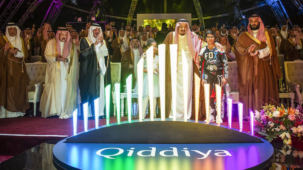 "Saudi King Salman bin Abdulaziz and Crown Prince Mohammed bin Salman embracing two children while standing behind the logo for ""Qiddiya"", an ""entertainment city"" spanning 334-square kilometres southwest of the capital Riyadh. (AFP)"