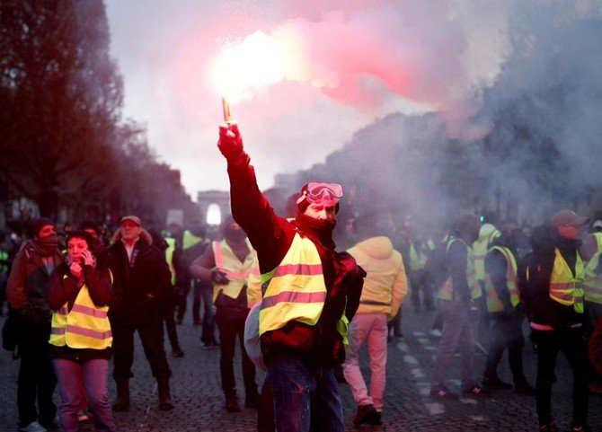 A protester wearing a yellow vest symbolizing French drivers' protest against higher fuel prices burns flare. (Reuters)