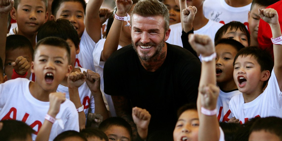 Former soccer player David Beckham stands with young footballers during the AIA football clinic for youths at the SCG Muangthong United Football Club in Bangkok, Thailand, November 3, 2018. REUTERS/Athit Perawongmetha