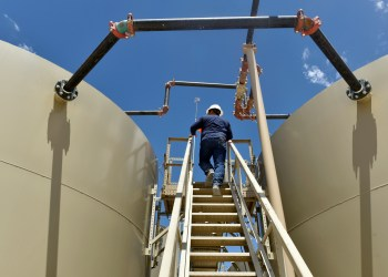 FILE PHOTO: Lease Operator Jon Pearson inspects oil tanks at a production facility owned by Parsley Energy in the Permian Basin near Midland, Texas U.S. August 23, 2018. Picture taken August 23, 2018. REUTERS/Nick Oxford/File Photo