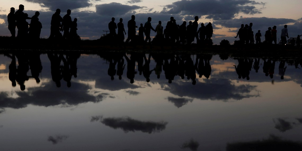 FILE PHOTO: Palestinian demonstrators are reflected in rain water after attending a protest calling for lifting the blockade on Gaza, at the Israel-Gaza border fence in Gaza October 26, 2018. REUTERS/Mohammed Salem