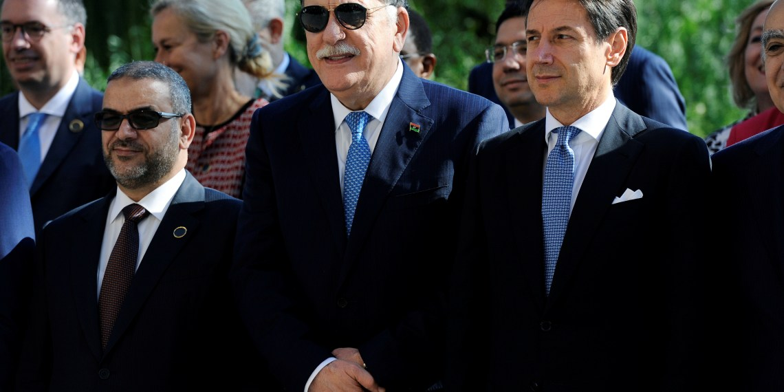 (L-R) President of Libya High Council of State Khaled Al-Mishri, Libya's Prime Minister Fayez al-Sarraj and Italy's Prime Minister Giuseppe Conte pose for a family photo during the second day of the international conference on Libya in Palermo, Italy, November 13, 2018. REUTERS/Guglielmo Mangiapane