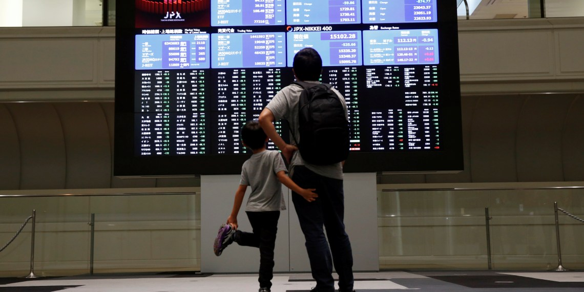 FILE PHOTO: Visitors look at a stock quotation board at Tokyo Stock Exchange in Tokyo Japan, October 11, 2018. REUTERS/Issei Kato