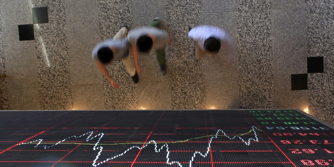 FILE PHOTO: People walk under an electronic board showing stock information at the Shanghai Stock Exchange in Lujiazui Financial Area before the visit of Britain's Chancellor of the Exchequer George Osborne in Shanghai, China, September 22, 2015. REUTERS/Aly Song