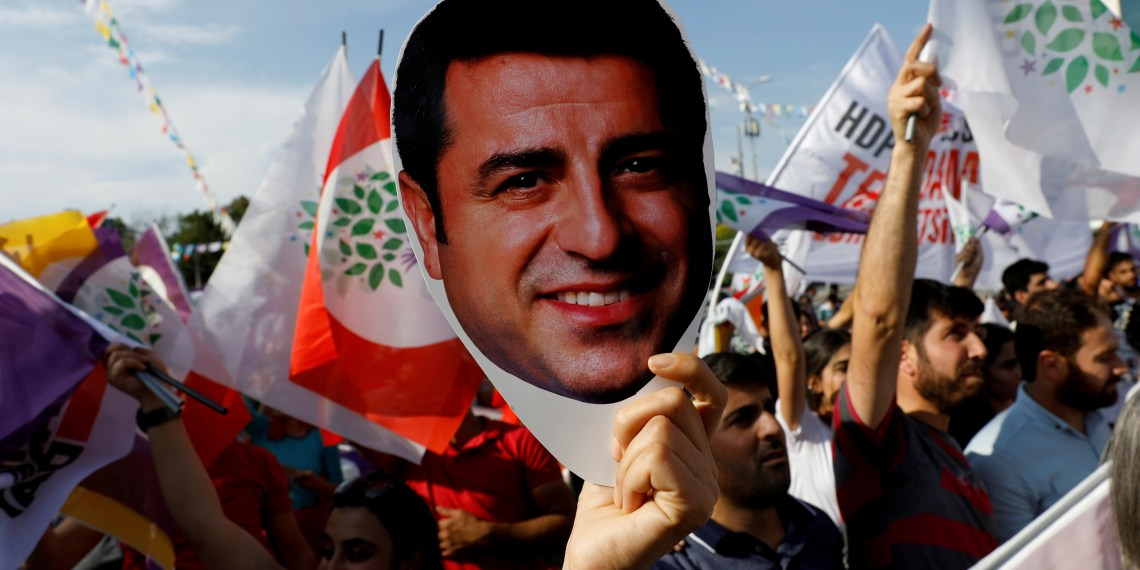 FILE PHOTO: A supporter of the pro-Kurdish Peoples' Democratic Party (HDP) holds a mask of their jailed former leader and presidential candidate Selahattin Demirtas during a rally in Ankara, Turkey, June 19, 2018. REUTERS/Umit Bektas