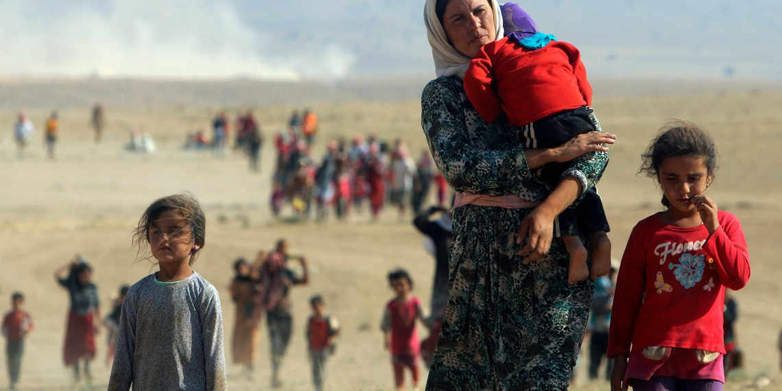 Displaced people from the minority Yazidi sect, fleeing violence from forces loyal to the Islamic State in Sinjar town, walk towards the Syrian border on the outskirts of Sinjar mountain near the Syrian border town of Elierbeh of Al-Hasakah Governorate in this August 11, 2014. REUTERS/Rodi Said/File Photo - S1AETKFHFEAA