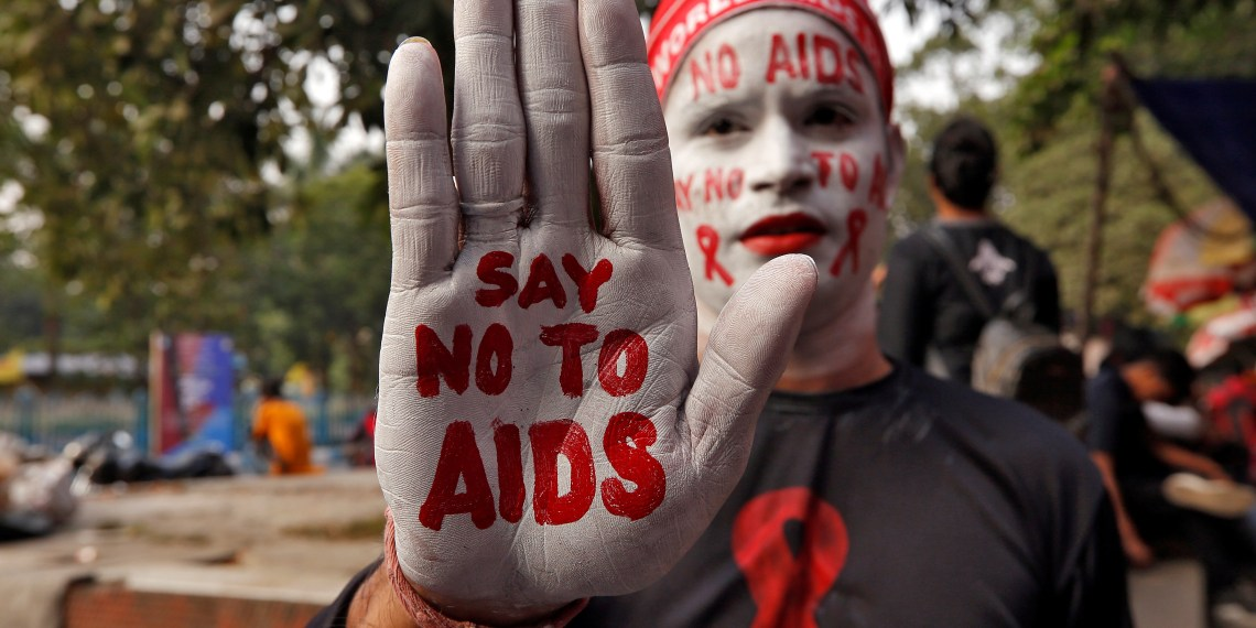 A man poses as he displays his hand and face painted with messages during an HIV/AIDS awareness campaign on the eve of World AIDS Day in Kolkata, India, November 30, 2018. REUTERS/Rupak De Chowdhuri - RC127FB93D70