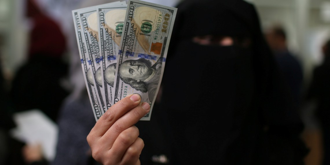 A Palestinian Hamas-hired civil servant displays U.S. Dollar banknotes after receiving her salary paid by Qatar, in Khan Younis in the southern Gaza Strip December 7, 2018. REUTERS/Ibraheem Abu Mustafa