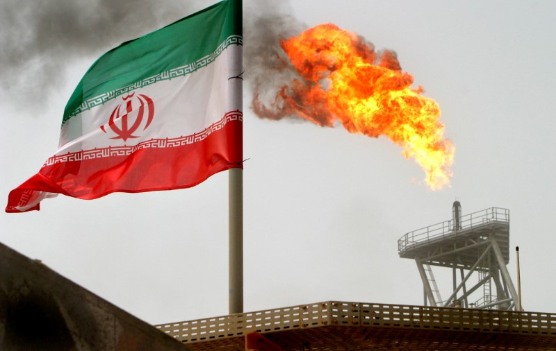 FILE PHOTO: A gas flare on an oil production platform in the Soroush oil fields is seen alongside an Iranian flag in the Persian Gulf, Iran, July 25, 2005. REUTERS/Raheb Homavandi