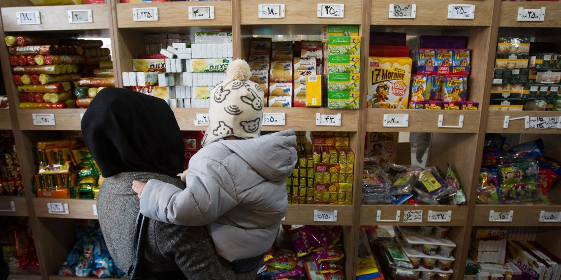 FILE PHOTO: A woman carrying her son stands in front of a food shelf as she shops at a supermarket in northern Tehran, December 12, 2011. REUTERS/Morteza Nikoubazl