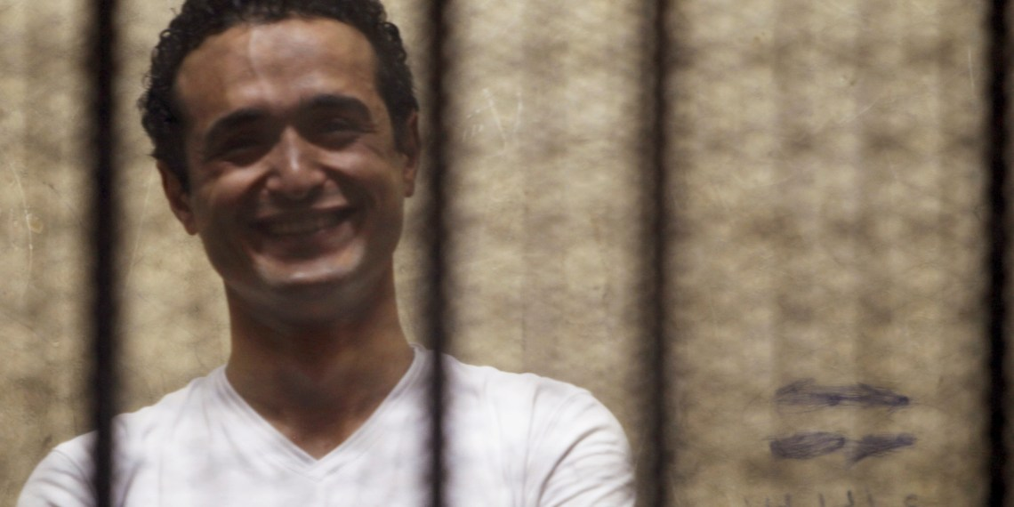 FILE PHOTO: Egyptian activist Ahmed Douma smiles from behind bars during his trial at the New Cairo court, on the outskirts of Cairo June 3, 2013. REUTERS/Amr Abdallah Dalsh/File Photo