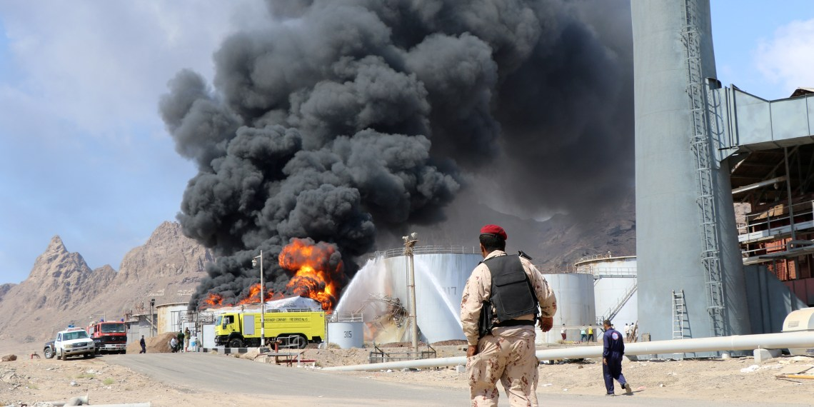 A soldier walks as fire engulfs an oil storage tank at the Aden oil refinery one day after an explosion in the refinery in Aden, Yemen January 12, 2019. REUTERS/Fawaz Salman