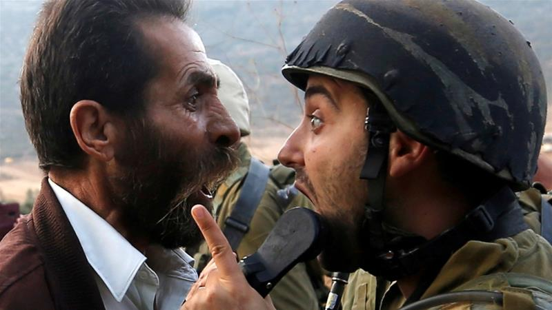 A Palestinian man argues with an Israeli soldier during clashes over an Israeli order to shut down a Palestinian school near Nablus in the occupied West Bank October 15, 2018 [File:M Torokman/Reuters]