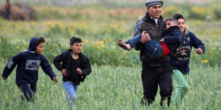 A Palestinian boy is evacuated after inhaling tear gas fired by Israeli forces during a protest at the Israel-Gaza border fence, in the southern Gaza Strip March 1, 2019. REUTERS/Ibraheem Abu Mustafa