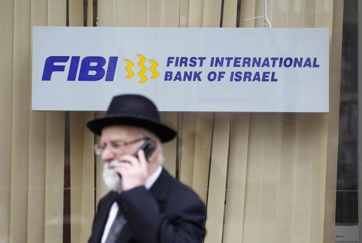 FILE PHOTO: A man speaks on his mobile phone as he walks in front of a First International Bank of Israel branch in Jerusalem January 27, 2014. REUTERS/Baz Ratner