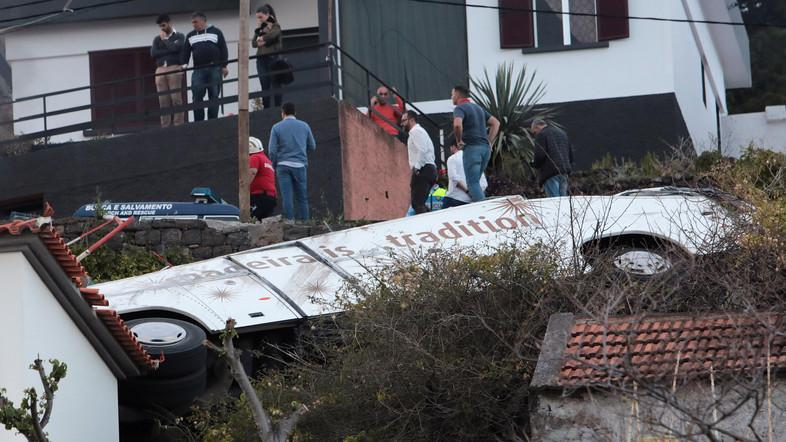 People stand next to the wreckage of a bus after the accident in the Portuguese Island of Madeira on April 17, 2019. (Reuters)