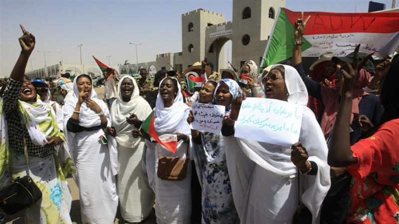 Sudanese women raise banners and a national flag as they rally outside the army headquarters in Khartoum [Ebrahim Hamid/ AFP]