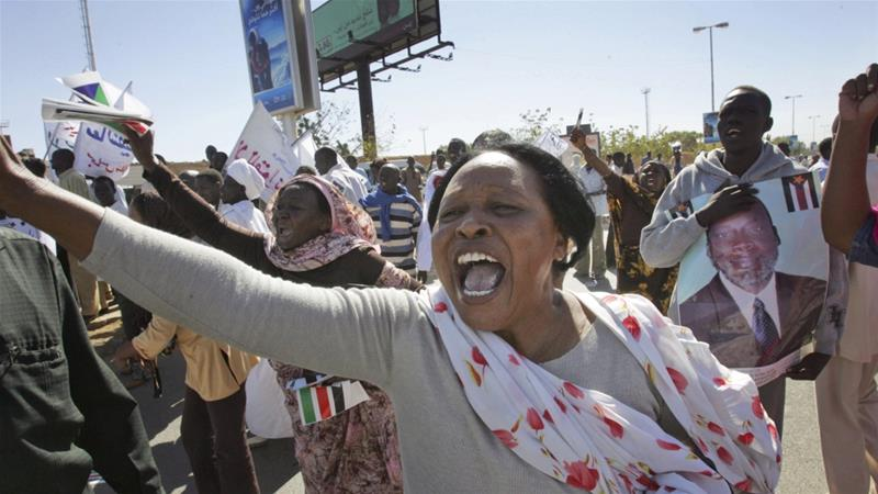 """On April 10, the photograph of 22-year-old engineering student Alaa Salah chanting in front of a crowd of protesters went viral, capturing the world's attention and breaking an international media blackout on Sudan's protests. She was quickly branded the """"symbol"""" of the Sudanese revolution, her image defying spurious normative ideas of Muslim women as oppressed and politically passive. The international media obsessed over her act of courage and exceptionalised it, missing a critical opportunity to look into the central role Sudanese women have played in the revolution so far and the broader historical context in which their activism has emerged. In fact, the history of Sudan has been dotted by iconic female figures: from the Kandaka (the Nubian queen) of Meroe, whose military strategy prevented Alexander the Great from conquering Nubian lands in 332 BC, to Dr Khalida Zahir, Sudan's first woman doctor who was arrested by the British in 1946 for opposing colonial rule, to Fatima Ibrahim a prominent communist and leader of the Sudanese Women's Union, who fought for women's right to vote, equal pay and maternity leave. It is important for us, two women from the Gezira and Darfur, to point out that while some of these feminist icons from central and northern Sudan have received recognition, the critical role working-class women and women from marginalised regions have played as drivers of popular resistance against dictatorship, political marginalisation and state violence in Sudan for decades has largely been overlooked. In this sense, Alaa is the daughter of not just prominent Sudanese feminists but also of generations of ordinary women from across Sudan who have been at the forefront of anti-regime resistance. Their fight for dignity and freedom has laid firm foundations from which now she and countless other young women protesters can step in their courageous struggle against the regime. Alaa Salah stands in front of a mural depicting her in Khartoum, on April 20, 2"""