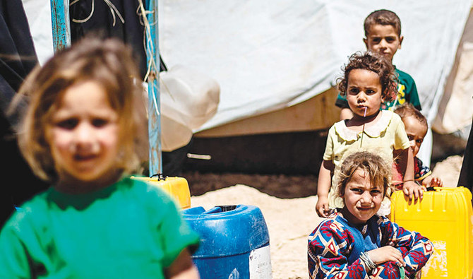 Displaced Syrian children from the eastern Deir Ezzor province, queue for water inside Al-Hol camp for displaced people in Al-Hasakeh governorate in northeastern Syria on May 28. (AFP)