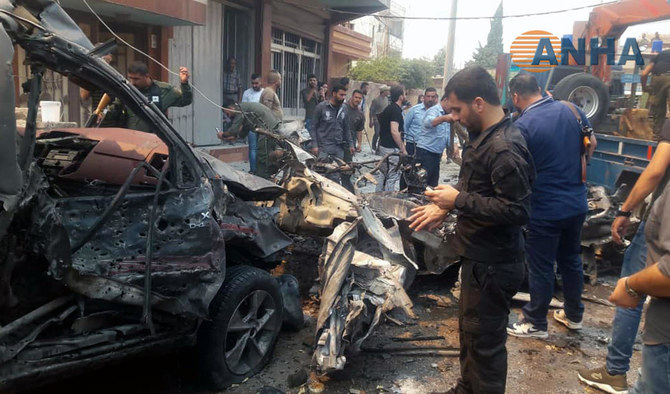 This image provided by Hawar News Agency, ANHA, an online Kurdish news service, shows people inspecting debris at the scene of a car bombing in the town of Qamishli, eastern Syria on Monday, June 17, 2019. (ANHA via AP)