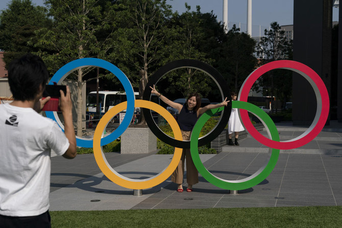 Tokyo residents Yuuma Sakai, foreground, takes photos of his wife, Hiroyo, with the Olympic rings set up near New National Stadium in Tokyo. (AP/Jae C. Hong)