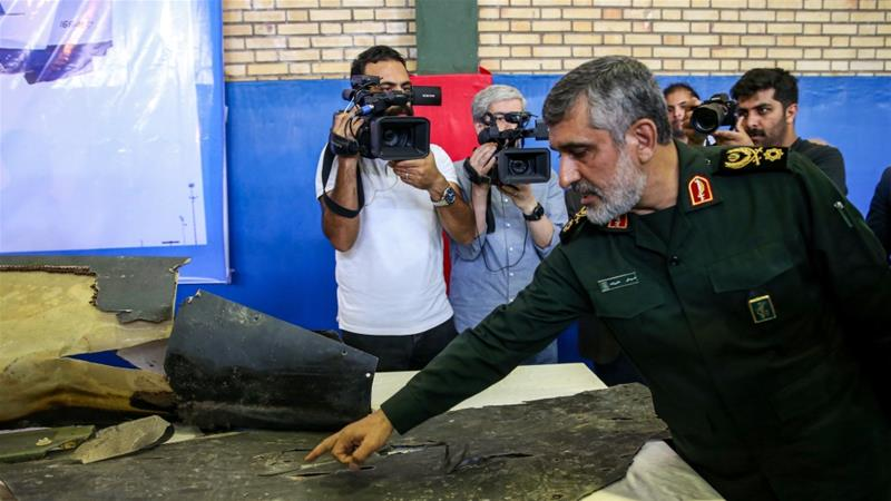 General Amir Ali Hajizadeh (R), head of IRGC's aerospace division, speaks to media next to debris from a downed US drone reportedly recovered within Iran''s territorial waters [Meghdad Madadi/ Tasnim News/ AFP]