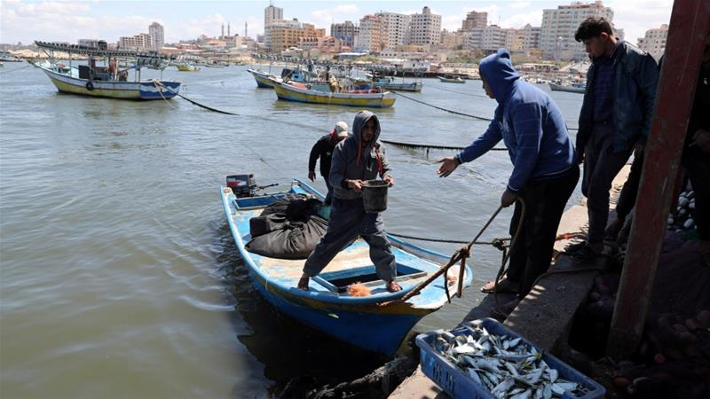 Palestinian fishermen unload their catch at the seaport of Gaza City [File: Mohammed Salem/Reuters]