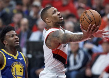 In this May 20, 2019 photo, Portland Trail Blazers guard Damian Lillard shoots near Golden State Warriors forward Jordan Bell during Game 4 of the NBA basketball playoffs Western Conference finals in Portland, Oregon. (AP Photo/Craig Mitchelldyer, File)