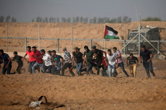 Palestinian demonstrators run away from the fence during protests along the border with Israel, east of Khan Yunis, in the southern Gaza Strip on July 12, 2019. (AFP)