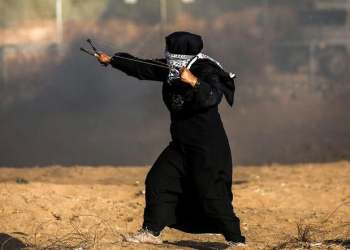 A Palestinian woman uses a slingshot to throw rocks during clashes with Israeli forces following a demonstration along the border with Israel east of Khan Yunis in the southern Gaza strip. (AFP)