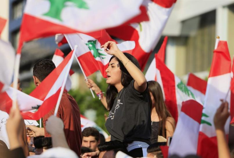 Demonstrators carry national flags during an anti-government protest in the port city of Sidon, Lebanon October 19, 2019. REUTERS/Ali Hashisho